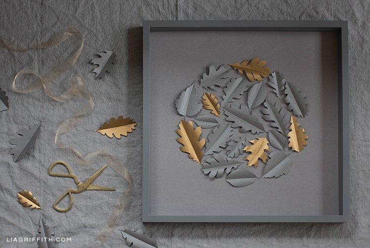 Papercut oak leaf framed art on grey sheet next to cutout leaves and scissors