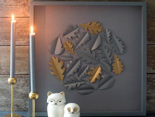 Papercut oak leaf framed art on mantle next to candles