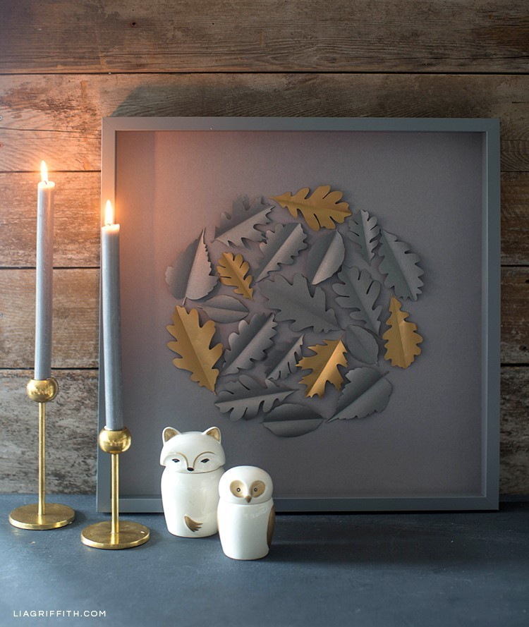 Papercut oak leaf framed art on mantle next to candles