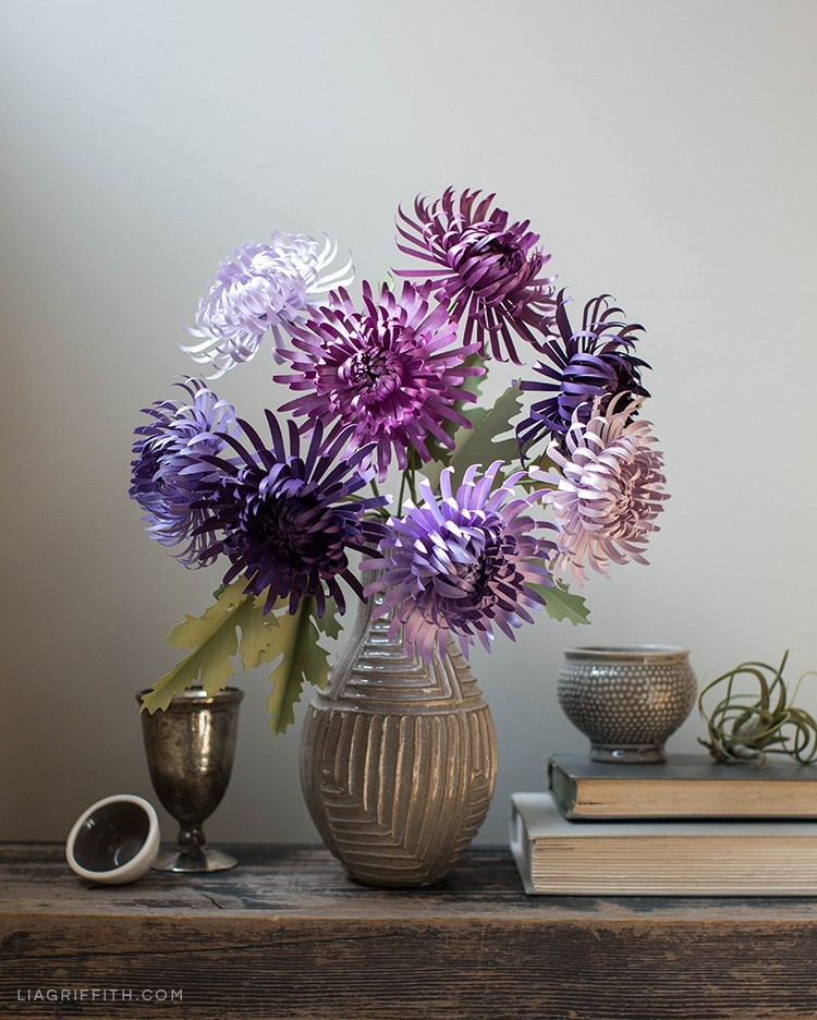 Purple paper spider chrysanthemums in vase next to books on table