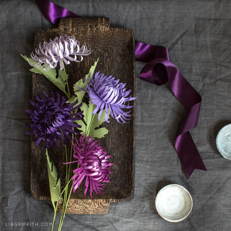 Purple paper spider chrysanthemums on wood tray next to purple ribbon
