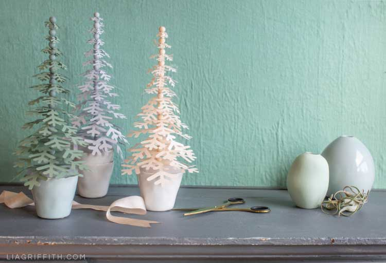 paper holiday trees in tiny pots on mantel with small vases, scissors, and ribbon
