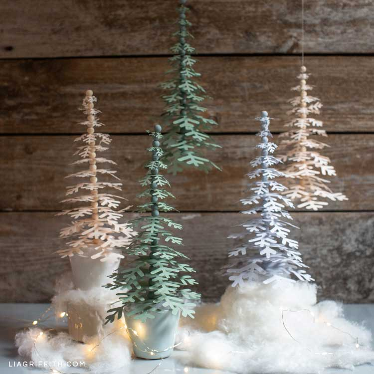 paper holiday trees on mantel with small lights and fake snow fluff